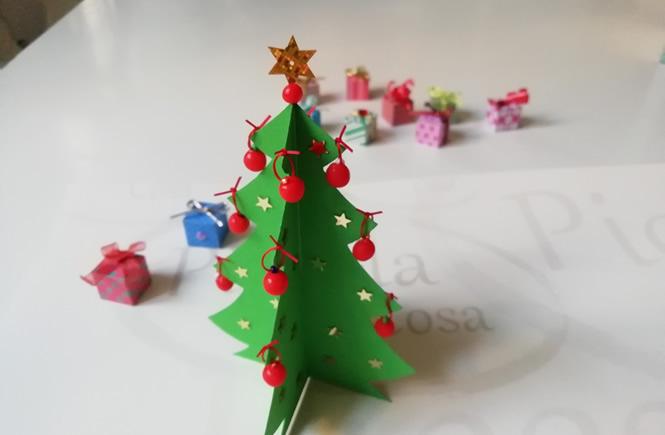 arbol de navidad de cartulina, con bolitas de plastilina en las puntas y estrellitas brillantes pegadas por el cuerpo del árbol. de fondo se ven pequeños regalos dabajo del árbol
