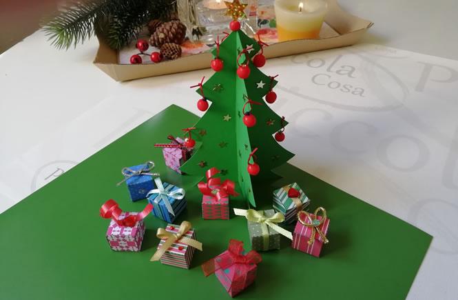 árbol completamente decorado con bolitas rojas, estellas brillantes y regalos a los pies del árbol