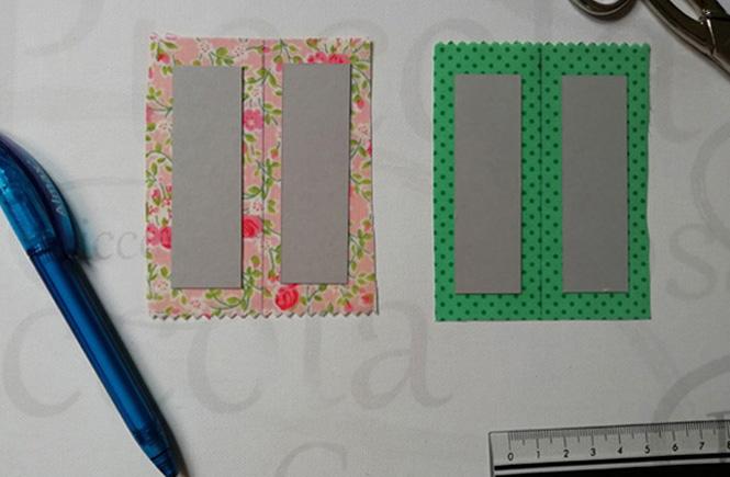 Cada rectángulo de cartulina se pone encima de un trozo de tela más grande que éste. Dos rectángulos con estampad de flores y los otros dos de color verde con lunares.