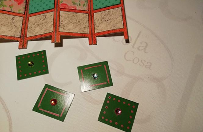 Detalle de los cuadros de cartulina verde con las piezas de cristal pegadas antes de pegarlos al biombo.