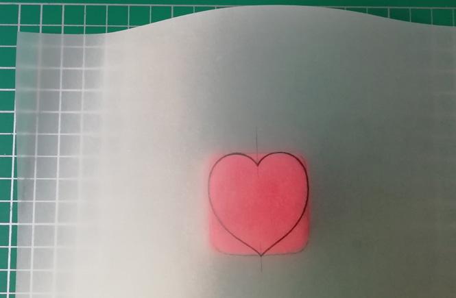 Colocamos el papel de calcar con el dibujo de un corazón, encima del bloque de las tres plastilinas de colores