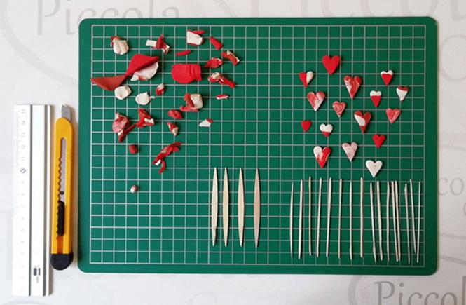 Pequeños corazones de plastilina de color rojo y blanco. Palillos planos cortados para pegar los corazones de plastilina.