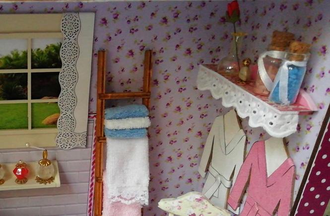 Estantería miniatura colgada de la pared del ambiente baño en miniatura.