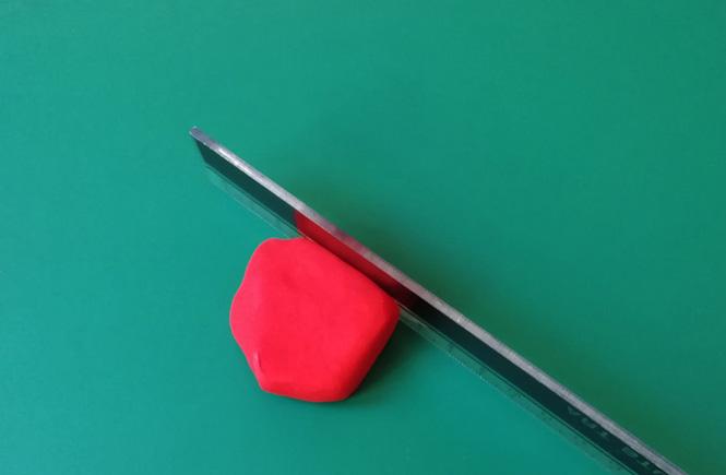 Empezamos cortando la plastilina roja con una regla metálica
