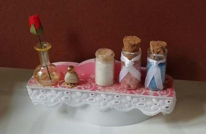 Estantería en miniatura forrada con el papel craft y la puntilla alrededor. Sales de baño, perfume y jarrón de cristal con rosa encima de la estantería.